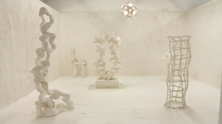 A group of white semi abstract sculptures in a white room by artist Nick Evans